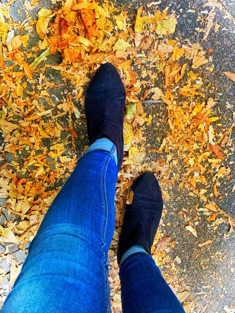 Herbstlaub und Stiefeletten